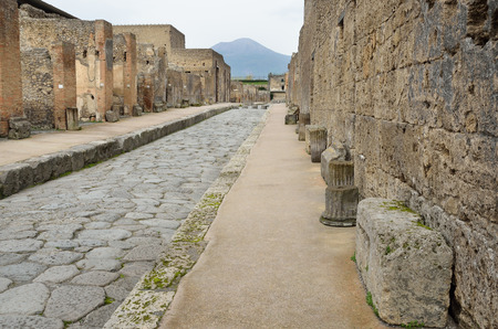 rehabilitated people: Ancient paved street is recovered in the middle of Roman ruins against the mountains. Stock Photo