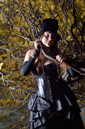 stove pipe: A teenage girl is photographed in the middle of the bare curved branches. She is wearing an anime costume of the undertaker. Stock Photo