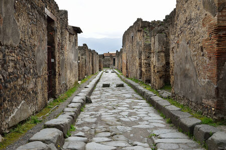regenerated: Narrow paved street is recovered in the middle of Roman ruins. Pompeii has been a popular tourist destination for over 250 years.