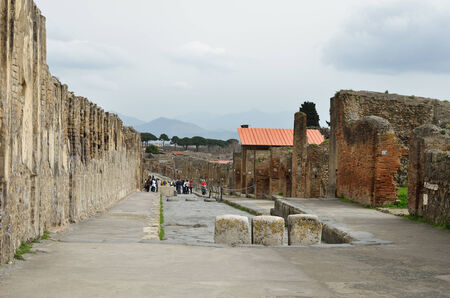 Group of tourists are sightseeing the rebuilt street in the Roman ancient city Pompeii. Editorial