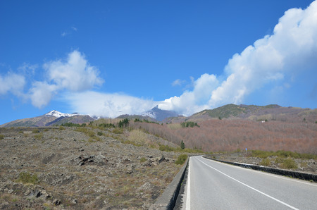 volcano slope: An asphalt road is running along the fertile flat slope. The peak of the active volcano Etna with smoke and a lot of clouds is towering in the background.