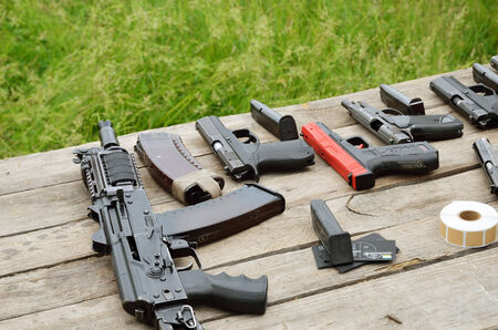 Rifles, pistols and other firearm are laid out on the table outdoors.