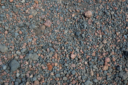scoria: Layer of the pyroclastic materials is photographed close-up. Various lapillistones or tephra cover the ground of the volcanic slopes. Stock Photo