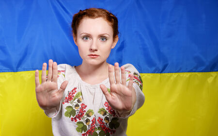 ukrainian ethnicity: The frightened young woman is making a gesture of defence against the national Ukrainian flag. She is wearing a shirt embroidered.