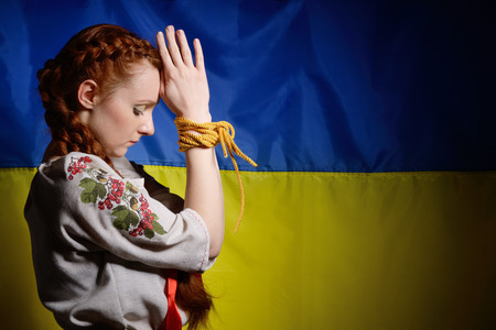 resolute: The resolute young woman is rising her bound arms against the national Ukrainian flag. She is wearing a shirt embroidered.