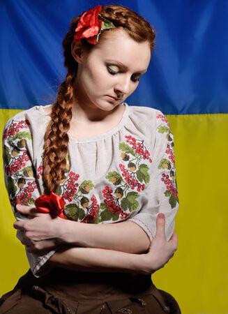 alicaído: La mujer joven triste lleva una camisa bordada. Su pelo rojo se trenzó con una cinta roja. Ella está de pie en contra de la bandera ucraniana nacional.