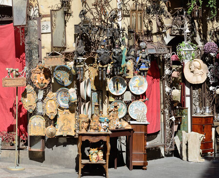 favours: Various souvenirs and mementos are offered for sale in the Sicilian street shop. There are wood marionettes, painted plates, statuettes and icons. Stock Photo
