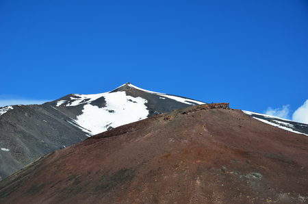 scoria: Small silhouettes of the tourists are on the lateral crater of the mount Etna  against the slope with snowfield.