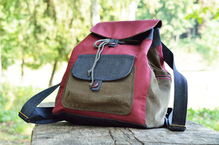packsack: The jean rucksack is on the wooden plank outdoors. It is hand-crafted and made of cotton and decorated with pockets. Stock Photo