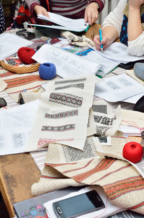 needlecraft: The table is covered with handmade samples, paper sheets, yarn and threads, pieces of cloth during the tuition of needlecraft. Stock Photo
