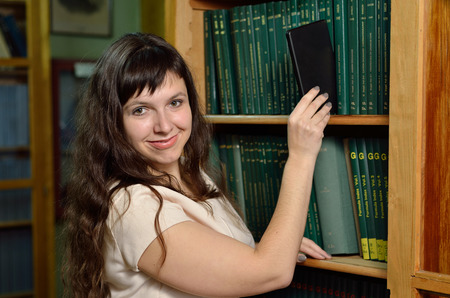 tomes: A young woman takes an electronic device from the shelf with scientific books.