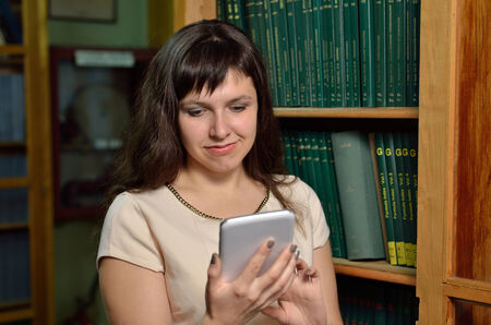 tomes: A young woman uses an electronic device against the shelves withlarge scientific books.