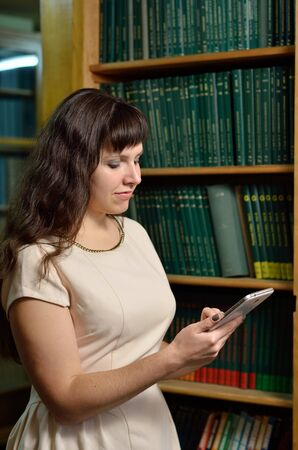 tomes: A young woman uses an electronic device against the shelves with large tomes of scientific journals. Stock Photo