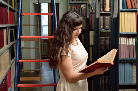 tomes: A young woman is reading a large book between the bookcases in the scientific library.