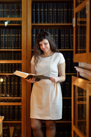 tomes: A happy young woman is reading a large tome under the tall bookcases in the scientific library.