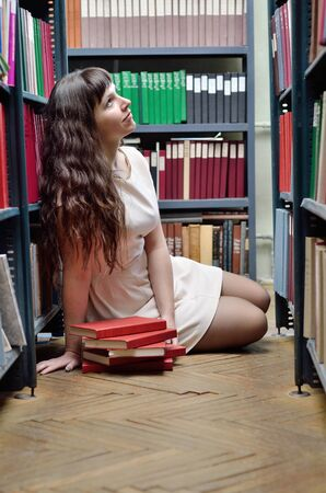 A young woman is sitting on the floor between the bookcases in the scientific library. photo