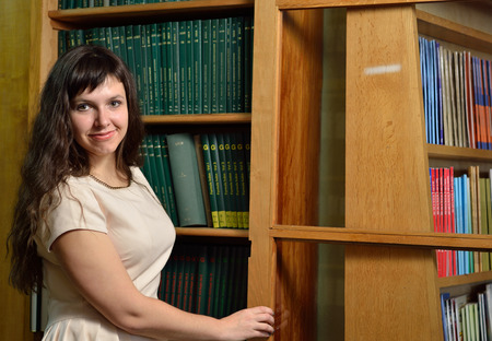A happy young woman is standing near the tall bookcase in the scientific library. photo