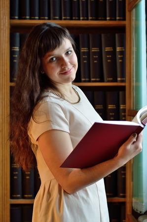 tomes: A happy young woman is holding a tome near the bookcase in the scientific library.