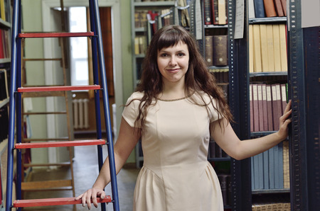 tomes: A young cheerful woman is standing in the middle of the bookcases in the library.
