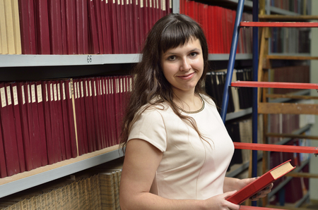tomes: A young cheerful woman is holding a scientist journal between the bookcases in the library. Stock Photo