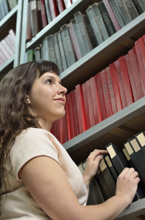A young cheerful woman is working the old scientific journals in the stillage. photo