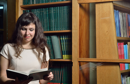 A happy young woman is reading a tome near the bookcase in the scientific library. photo