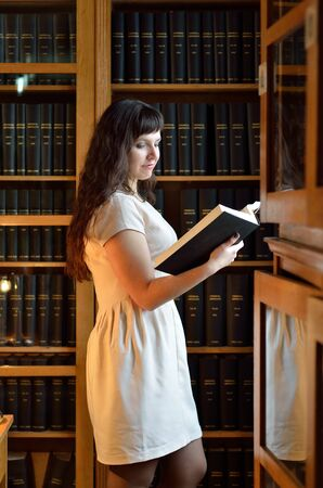 tomes: A happy young woman is reading a tome near the bookcase in the scientific library.