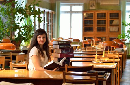 tomes: A young woman is sitting with a large pile of the scientific books in the atheneum.