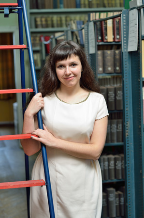 tomes: A young cheerful woman is standing near the ladder in the library.