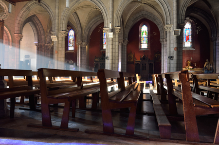 settles: The sunbeams light the wooden benches in the empty cathedral. Editorial
