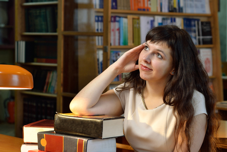 tomes: A pensive young woman is based on the pile of the heavy books. Stock Photo