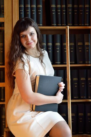 book racks: A happy young woman is holding a heavy tome near the bookcase in the scientific library. Stock Photo