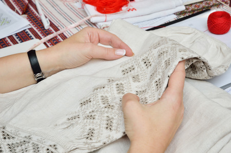 homespun: Female hands hold the homespun linen sleeve embellished with cutwork embroidery.