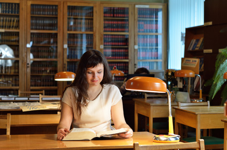 tomes: A young woman is reading a large book in the reading-room of a scientific library.