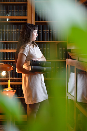 A thoughtful student is holding the big books near the bookcase in the scientific library. There are blurred leaves in the foreground. photo