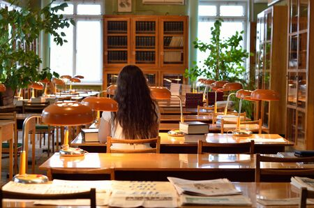 A young woman is sitting with a large pile of the scientific books in the atheneum.