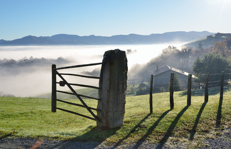 shrouded: The slopes are shrouded with mist in the winter sunny day. A farm with a green pasture is situated on the forested mountain in the Pays Basque. Stock Photo