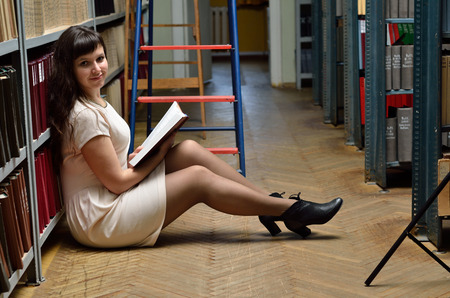 A young woman is sitting on the floor between the bookstands in the scientific library. She holds a book. photo