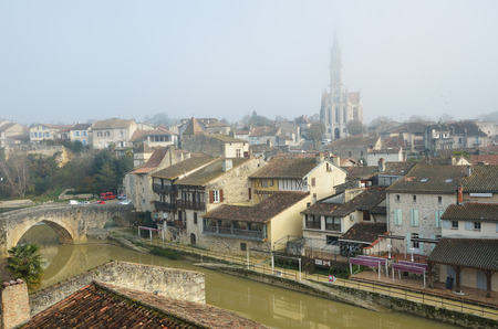 the silence of the world: Nerac is the ancient French town lying on both sides of the Baise River. The medieval buildings and the old bridge are reflected on the mirror surface of the calm water.
