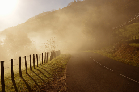 atmospheric phenomena: The mountain slope is covered with mist in the winter sunny day. There is a country road along the green pastures in the Pays Basque. Stock Photo