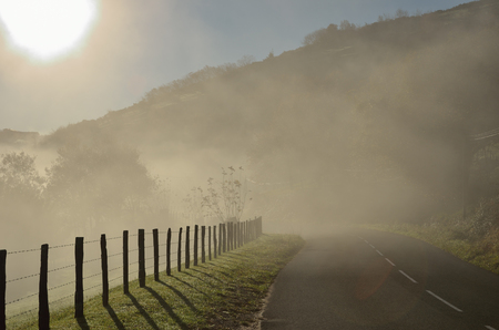 pays: The mountain slope is covered with mist in the winter sunny day. There is a country road along the green pastures in the Pays Basque. Stock Photo