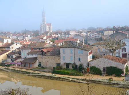 townhouses: Nerac is the ancient French town lying on both sides of the Baise River. There are medieval townhouses and the cathedral in the winter mist. Stock Photo