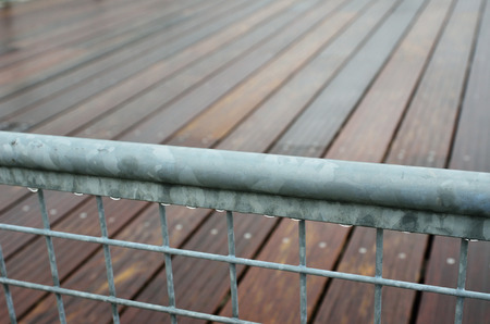 metal handrail: The wet metal banisters of the batten platform are photographed closely.