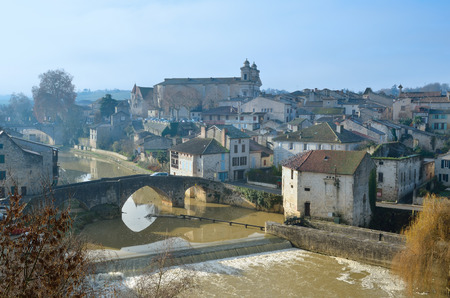 townhouses: There are old townhouses an ancient bridge and a medieval cathedral in the French town Nerac lying on both sides of the Baise River. Stock Photo