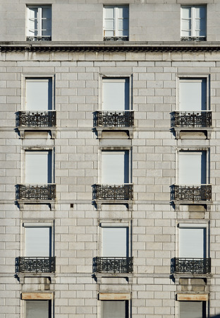 jalousie: Many identical windows are closed with alike external jalousie and decorated with similar small balconies on the wall.