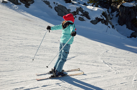 compacted: A skiergirl is sliding down on the ski run of compacted snow.