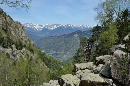tourism in andorra: The mountain slope with a moraine is photographed in the national park Vall-de-Madriu-Perafita-Claror. There are the valley, remote peaks covered with snow in the background.