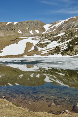 snow fields: The alpine lake is covered with ice and surrounded with snow fields. The sky and spring mountains are reflected in the transparent water.