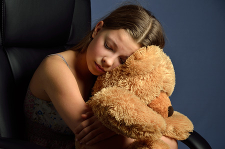 necking: The blonde girl put her head on the big teddy bear and closed her eyes. She is cuddling the soft fluffy toy close in the armchair. Stock Photo
