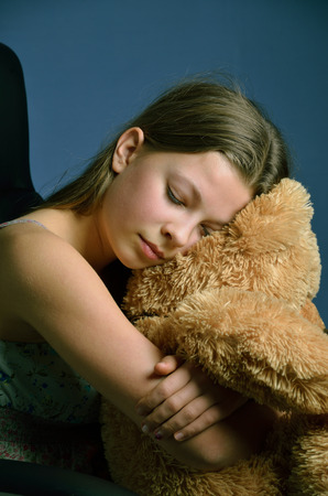 necking: The blonde girl put her head on the big teddy bear and closed her eyes. She is cuddling the soft fluffy toy close.